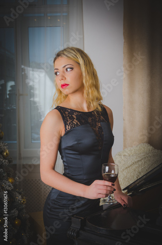 A Glass Of Wine An Attractive Girl In A Black Dress By The Piano