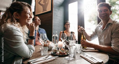 Fotobehang Restaurant Group of friends enjoying an evening meal at a restaurant