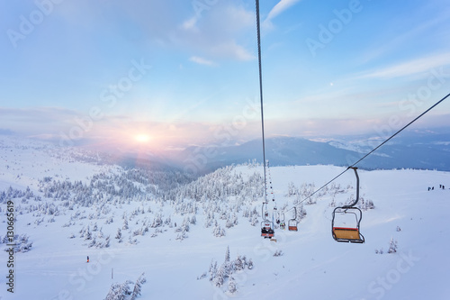 Ski lift with seats going over the mountain and paths from skies