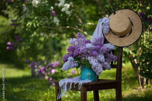 Foto op Plexiglas Lilac Bouquet of lilacs in a vase on a chair in the garden