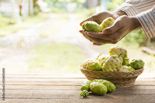 Noni fruit and noni basket on wooden table Wallpaper Mural