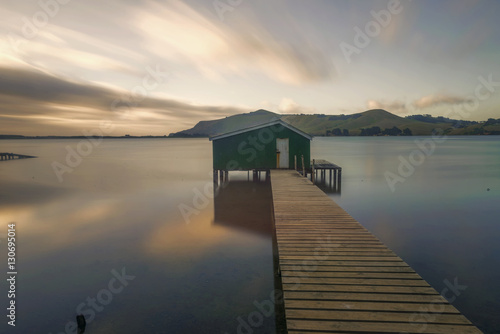 Photo  Otago peninsula coastal landscape scenery with green boat shed in sheltered wate