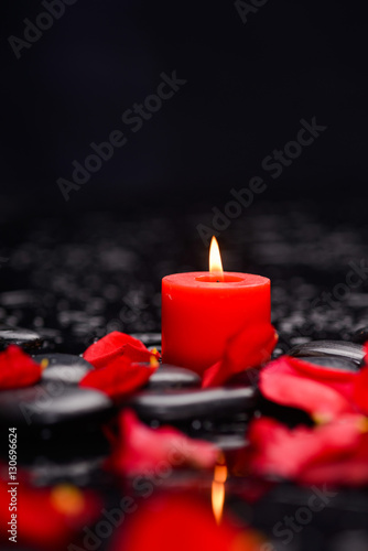 Obraz na plátně  Many rose petals with red candle and therapy stones