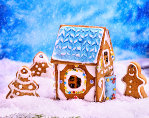 Gingerbread man , house near tree Christmas cookie with blue sky and falling winter snow. Xmas food decoration.