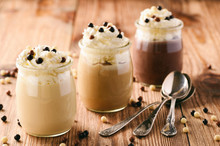 Milk, Toffee And Chocolate Pudding With Whipped Cream On Brown Wooden Background.