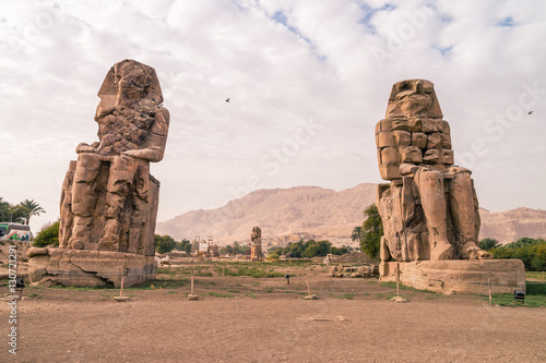 Photo Stands Egypt LUXOR: Ancient Colossi of Memnon in Egypt at noon. The original function of the Colossi was to stand guard at the entrance to Amenhotep's memorial temple.