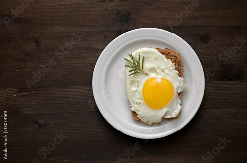 Fond de hotte en verre imprimé Ouf fried egg with rosemary on a white plate