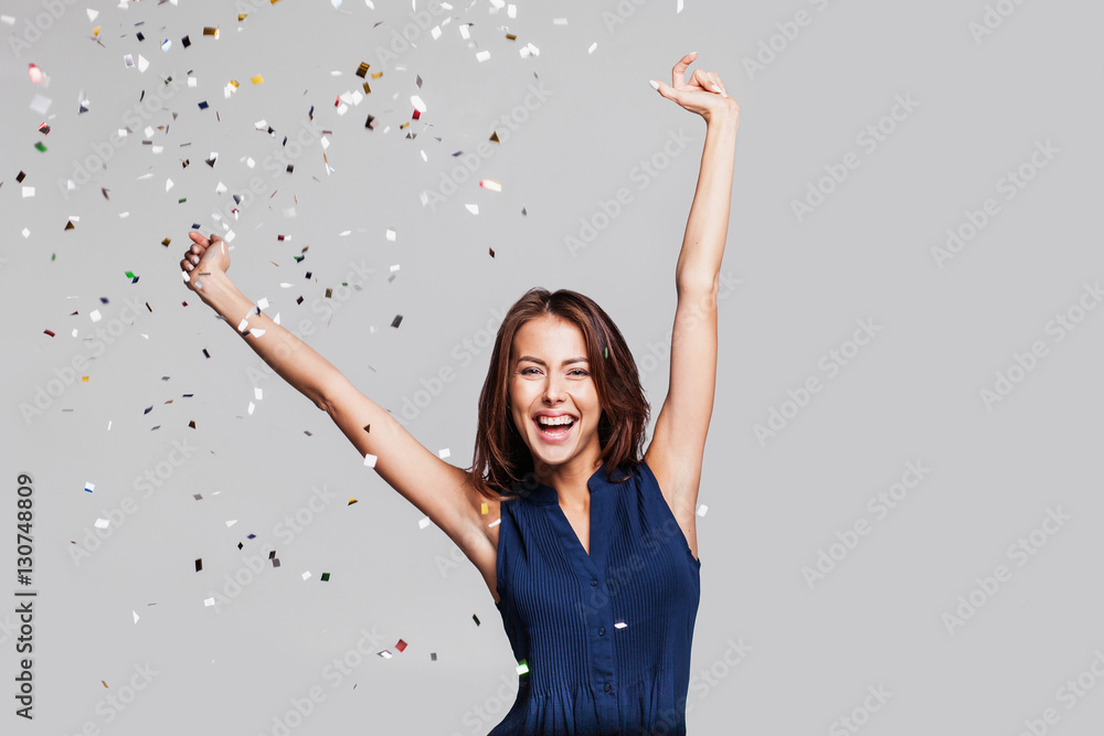 Fototapety, obrazy: Beautiful happy woman at celebration party with confetti falling everywhere on her. Birthday or New Year eve celebrating concept