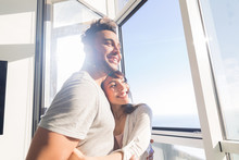 Young Couple Embrace Modern Apartment Big Panoramic Window Sea View, Mix Race Man And Woman Morning Home Interior