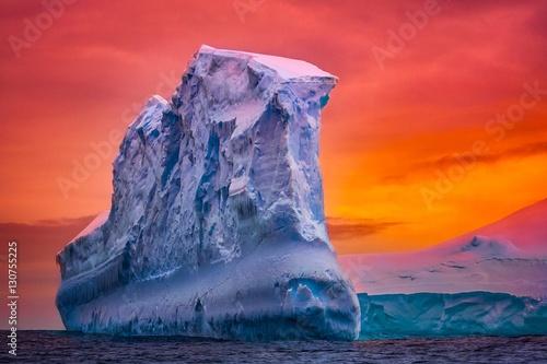 Foto auf Gartenposter Antarktika Antarctic iceberg in the snow floating in open ocean. Red sunset sky in the background. Beauty world