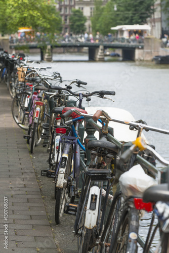 Photo  A number of bicycles parked at one of the sides of a canal.