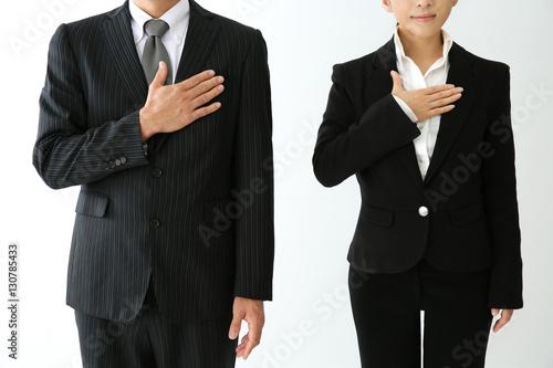Valokuva  胸に手をあてるスーツ姿の男女
