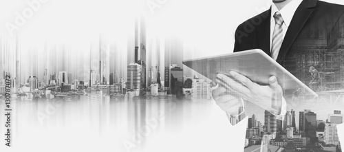 Fototapeta Businessman working on digital tablet, with double exposure city and real estate site construction, business development concept  obraz