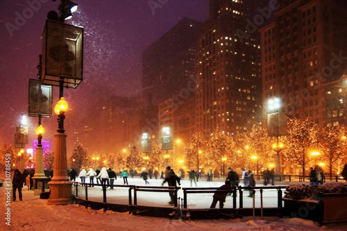 Foto op Canvas Chicago Winter night in Chicago. People enjoying ice skating at Millennium park ice rink during snowy night in Chicago.