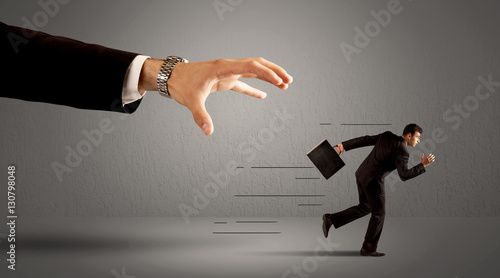 Photo Businessman running away from a huge hand