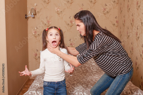 Fototapeta  Mother trying to strangle her little daughter.