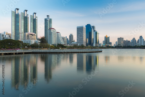 Spoed Foto op Canvas Abu Dhabi Office building with reflection over the lake in public park