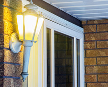Elegant Ornate Porch Light Glowing By Front Door, Welcoming