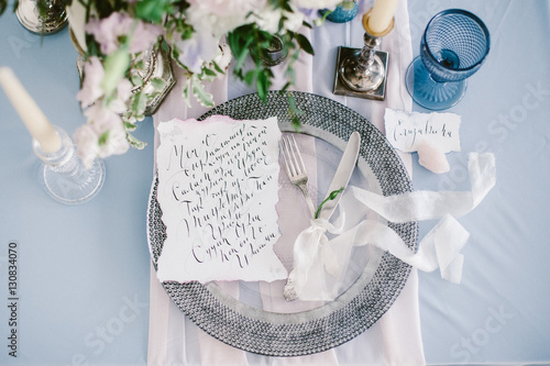 Fotografía  Graphic arts of beautiful wedding calligraphy cards and silver plate with cutlery on festive wedding table
