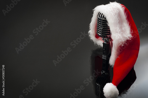 Fényképezés  Carols and Christmas music concept with a microphone wearing a santa hat with co
