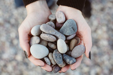 Woman Holding Smooth Pebbles On Rocky Beach