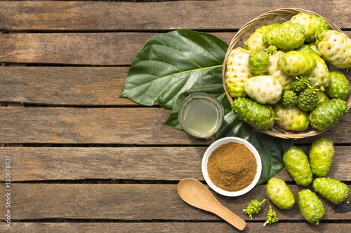 Noni fruit and noni in the basket with noni juice and noni powder on wooden table Wallpaper Mural