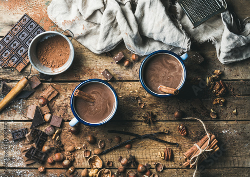 Foto op Plexiglas Chocolade Hot chocolate with cinnamon sticks, anise, nuts and cocoa powder on rustic wooden background, top view, horizontal composition