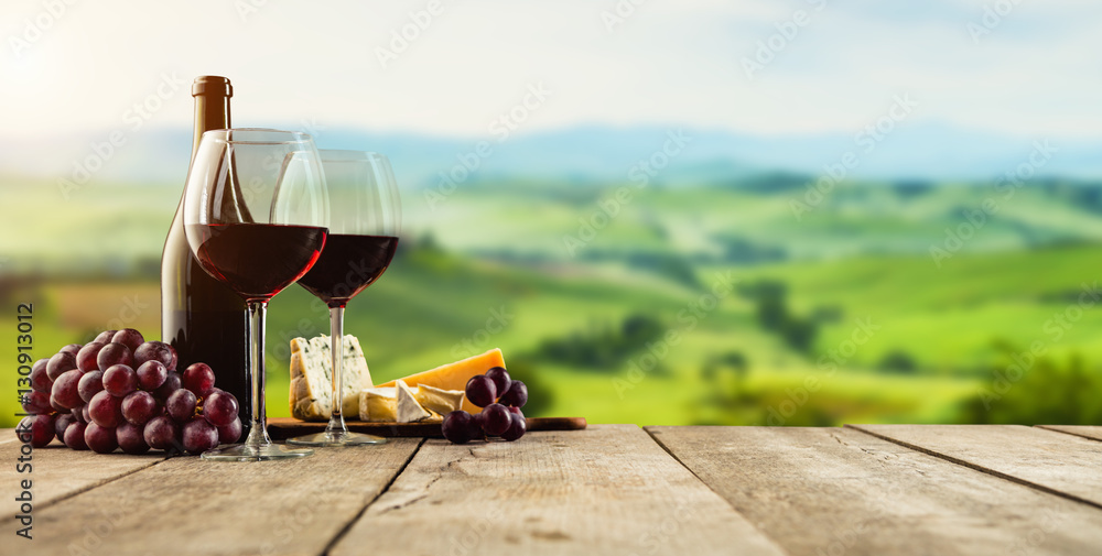 Red wine served on wooden planks, vineyard on background