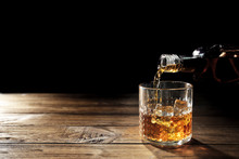 Pouring Whisky Into Glass On Wooden Table Closeup