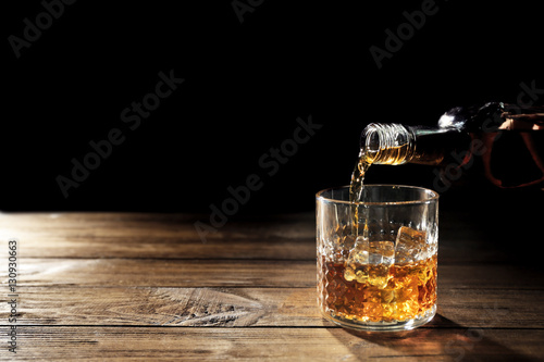 Photo sur Aluminium Cocktail Pouring whisky into glass on wooden table closeup