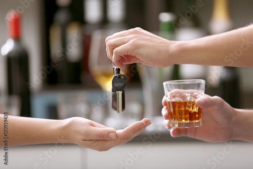 Fotografie, Obraz  Drunk man giving car key to woman, on blurred background