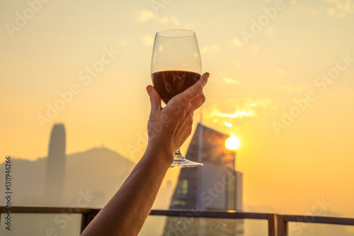 Photo  Close up of glass of red wine raised with the background the spectacular Hong Kong skyline at sunset