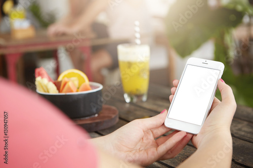 People, technology and leisure concept. Young female making video call to her friend on smart phone, using free wireless internet connection at coffee shop, sitting at table with cocktail and fruits