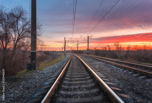 Spoed Foto op Canvas Grijze traf. Railway station against beautiful sky at sunset. Industrial landscape with railroad, colorful blue sky with red clouds. Railway junction. Heavy industry. Cargo shipping. Railway sleepers in dusk