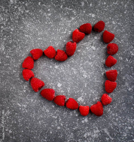 Valokuva  Raspberries in a heart shape on a stone background
