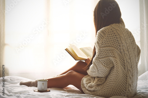 Fotografie, Obraz  Young woman sitting in bed while reading a book