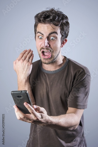 Fotografie, Obraz  Stressed angry man is shouting at his cell phone, irritated with the service