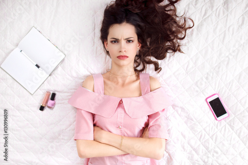 Photo Pouted woman lying with crossed hands on bed top view