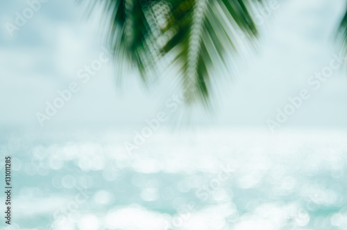 Keuken foto achterwand Lichtblauw Blur beautiful nature green palm leaf on tropical beach with bokeh sun light wave abstract background.