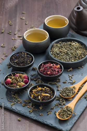 Spoed Foto op Canvas koffiebar assortment of dry tea in bowls, vertical, top view