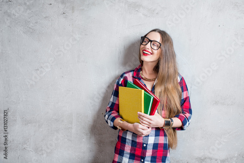 Fotografia  Portrait of a young happy student in checkered shirt with books on the gray wall