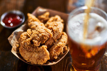 Focus On Fried Chicken Tenders In Basket With Beer Being Poured In Foreground