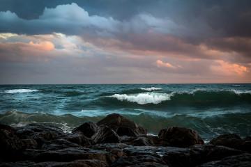 Fototapetal'écume des vagues d'une mer verte sous le ciel orageux, et près de rochers noirs
