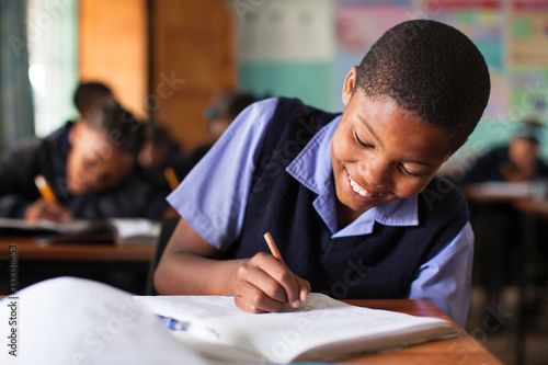 Young boy doing class work at a desk in a classroom in South Africa.