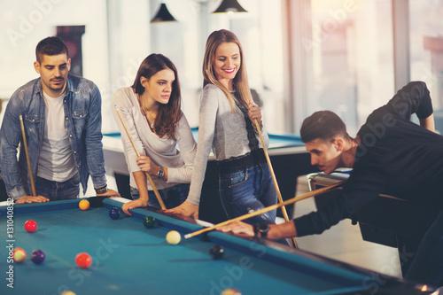 Plakat Grupa młodzi przyjaciele bawić się bilard