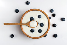White Yogurt In Natural Wooden Bowl With Blueberries. Top View On White Background.