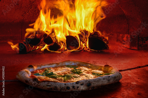Foto op Aluminium Pizzeria Italian pizza making dough stretching olive oil mozzarella cheese wood fire oven