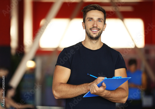 Portrait of personal trainer holding clipboard with training plan in gym Fototapeta