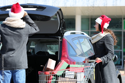 Canvas Prints Athens Young couple loading Christmas purchases into car trunk on shopping mall parking