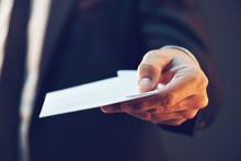 Businessman Offering Cash Money In Envelope As Bribe
